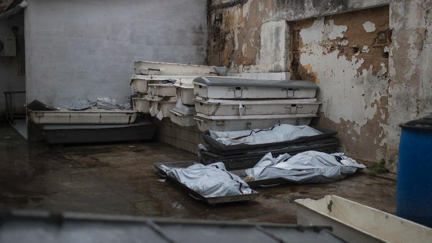 In this Jan. 22, 2017 photo, the bodies of three inmates who were killed in the Alcacuz prison massacre lay outside the morgue in Natal, Brazil. For the families of the more than 130 men killed in Brazilian prisons since the beginning of the year, suffering has been compounded by the government responses that range from sluggish to crass, a product both of limited resources and the disdain many Brazilians feel for prisoners in a country plagued by violence. (AP Photo/Felipe Dana)