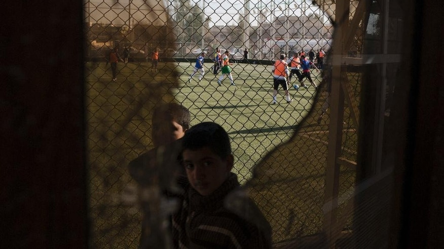 In this Wednesday, Feb. 8, 2017 photo, a child passes a broken window, damaged by fighting between Iraqi forces and Islamic State militants, while Mosul residents play soccer in the background. After months of fighting, Mosul residents can finally practice their favorite game again at the soccer field in the eastern part of the city—and this time without the changes imposed by Islamic State militants. (AP Photo/Bram Janssen)