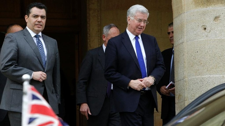 "British Defense Minister Michael Fallon, right, and with his Cyprus' counterpart Christoforos Fokaides, left, leave after the meeting with Cypriot President Nicos Anastasiades at the presidential palace in capital Nicosia, in the eastern Mediterranean island of Cyprus, on Friday, Feb. 10, 2017. Britain's defense secretary says the role played the UK's two military bases on Cyprus are ""more important than ever"" because of the rise of extremist terror and mass migration flows coming from the region. (AP Photo/Petros Karadjias)"