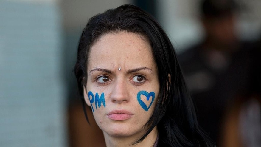A woman with her face painted joins relatives of military police members as they block an entrance in an attempt to impede officers from going to work at a military police in Rio de Janeiro, Brazil, Friday, Feb 10, 2017. The family members are demanding better salaries and labor conditions and they block the exits not allowing the officers to go work. Brazil's military police force patrols the nation's cities and its members are barred by law from going on strike. (AP Photo/Silvia Izquierdo)