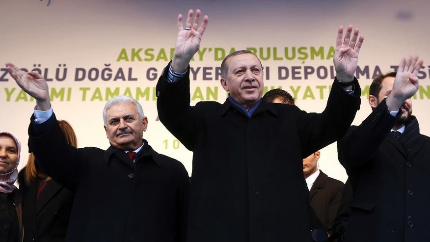 Turkish President Recep Tayyip Erdogan, center, and Prime Minister Binali Yildirim, left, salute supporters during a rally in Aksaray, Turkey, Friday, Feb. 10, 2017. Erdogan on Friday approved holding a national referendum on constitutional reforms that would usher in a powerful presidency. Erdogan signed off on the bill, paving the way for the country's electoral board to set a date for the referendum. (Kayhan Ozer/Presidential Press Service, Pool Photo via AP)