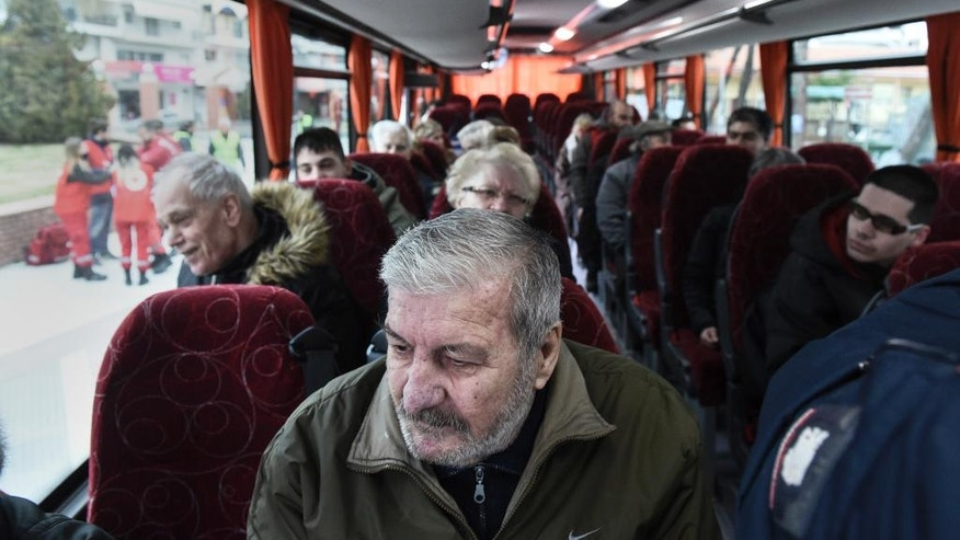 Residents of Kordelio district are seen aboard a bus after authorities ordered the evacuation of the area in order to defuse a 500-pound unexploded World War II bomb, in Thessaloniki, Greece Sunday, Feb. 12, 2017. Bomb disposal experts are to tackle the device, found buried beneath a gas station, on Sunday in an operation expected to last about six hours, with all residents in a nearly 2-kilometer (1.2-mile) radius being evacuated. (AP Photo/Giannis Papanikos)