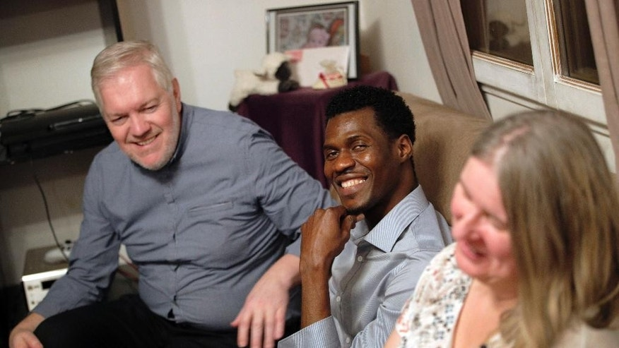 In this photo dated Thursday, Feb. 2, 2017, Loic Gandais, left, and his wife Murielle Gandais, right, sit in the living room with Cheikh Ahmed, a refugee from Guinea staying at their home in Palaiseau, south of Paris France. When the Gandais family decided to host a refugee at their home in a middle class neighborhood outside Paris, they assumed their guest would be a Syrian or an Iraqi fleeing war. Instead, a 25-year-old journalist with a young family in the former French colony of Guinea is the person sleeping gratefully in a spare bedroom, sharing unfamiliar food and nourishing hopes for a better life. (AP Photo/Christophe Ena)