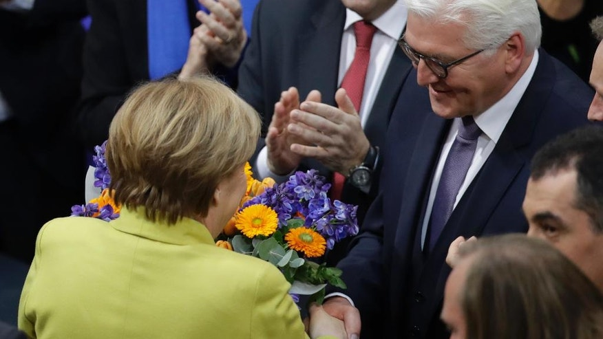 Newly elected German President Frank-Walter Steinmeier, right, is congratulated by German Chancellor Angela Merkel when a German parliamentary assembly came together to elect the country's new president in Berlin, Germany, Sunday, Feb. 12, 2017. (AP Photo/Michael Sohn)