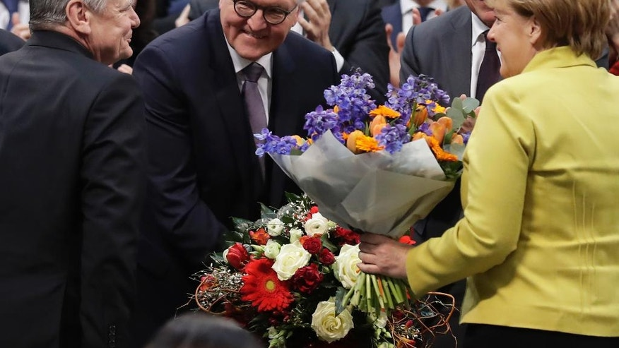 Newly elected German President Frank-Walter Steinmeier, second from left, is congratulated by German President Joachim Gauck, left, and German Chancellor Angela Merkel when a German parliamentary assembly came together to elect the country's new president in Berlin, Germany, Sunday, Feb. 12, 2017. (AP Photo/Markus Schreiber)