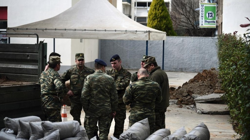 Military officers stand at a gas station in the northern Greek city of Thessaloniki, on Thursday, Feb. 9, 2016 where an unexploded World War II bomb was found 5 meters (over 16 feet) deep. Authorities in Greece's second-largest city on Sunday are planning to evacuate up to 60,000 residents from their homes so experts can safely dispose of the unexploded World War II bomb. (AP Photo/Giannis Papanikos)
