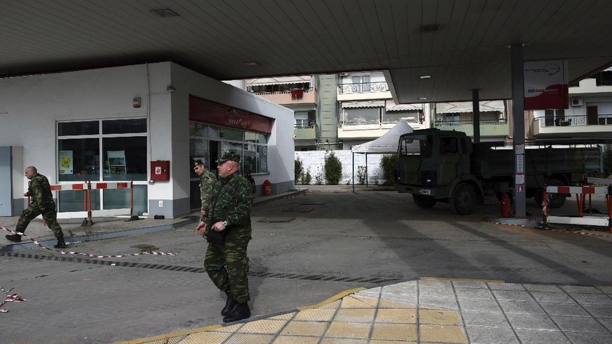Military officers leave a gas station in the northern Greek city of Thessaloniki, on Thursday, Feb. 9, 2016 where an unexploded World War II bomb was found 5 meters (over 16 feet) deep. Authorities in Greece's second-largest city on Sunday are planning to evacuate up to 60,000 residents from their homes so experts can safely dispose of the unexploded World War II bomb. (AP Photo/Giannis Papanikos)