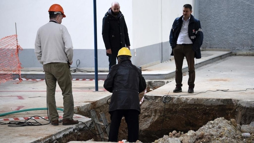 Experts check the location where an unexploded World War II bomb was found 5 meters (over 16 feet) deep, at a gas station in the northern Greek city of Thessaloniki, on Thursday, Feb. 9, 2016. Authorities in Greece's second-largest city on Sunday are planning to evacuate up to 60,000 residents from their homes so experts can safely dispose of the unexploded World War II bomb. (AP Photo/Giannis Papanikos)