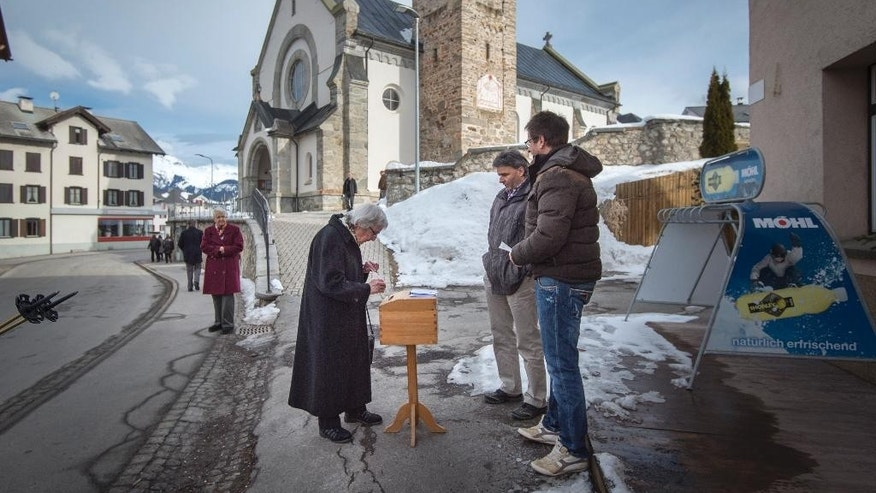 "A lady casts her vote in Obersaxen, Switzerland, Sunday Feb. 12, 2017. Swiss voters were deciding Sunday whether to make it easier for ""third-generation foreigners"" to get Swiss citizenship and whether to lock in competitive low tax rates for foreign companies in Switzerland. (Benjamin Manser/Keystone via AP)"
