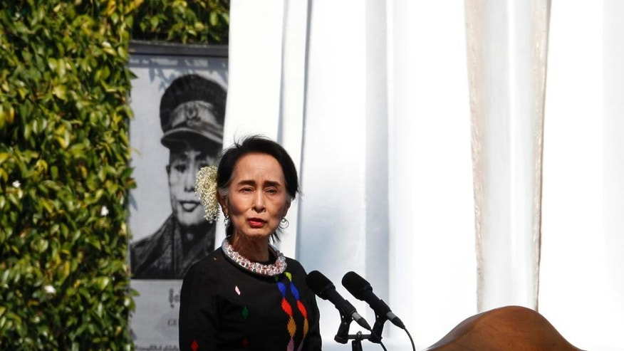 Myanmar State Counsellor Aung San Suu Kyi, standing by a portrait of her late father and national hero Gen. Aung San and the Panglong monument, delivers a speech during a ceremony to mark the 70th anniversary of Union Day Sunday, Feb.12, 2017, in Panglong, Southern Shan State, over 800 kilometers (500 miles) northeast of Yangon, Myanmar. (AP Photo/Thein Zaw)