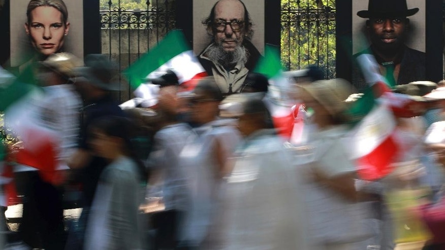Demonstrators walk past an outdoor photo exhibit during a march demanding respect for Mexico and its migrants, in the face of perceived hostility from the administration of U.S. President Donald Trump, in Mexico City, Sunday, Feb 12, 2017. About 20,000 people marched, many dressed in white, some carried Mexican flags, as a sign of unity. (AP Photo/Christian Palma)