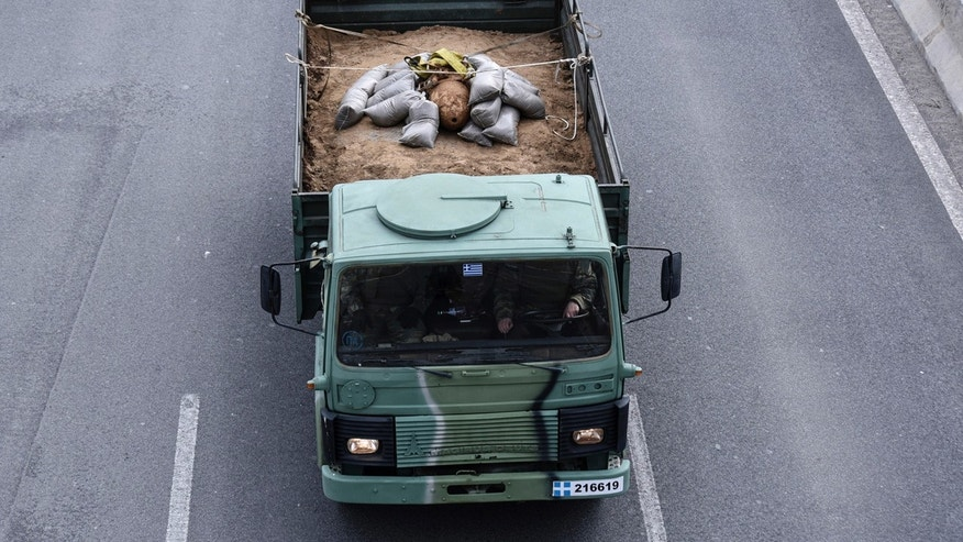 A military truck carries an unexploded World War II bomb which was defused by Greek Army personnel in Thessaloniki, Greece Sunday, Feb. 12, 2017.