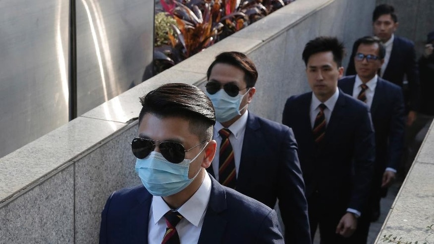 Five of the seven Hong Kong police officers, from left, Police Constable Wong Wai-ho, Police Constable Lau Hing-pui, Senior Inspector Lau Cheuk-ngai, Sergeant Pak Wing-bun and Police Constable Kwan Ka-ho arrive the District Court in Hong Kong Tuesday, Feb. 14, 2017 as they were charged with assaulting a pro-democracy activist in an incident on Oct. 15 2014. Seven Hong Kong police officers have been found guilty of a lesser charge in the assault of a pro-democracy activist whose videotaped beating during the height of 2014 pro-democracy protests sparked outrage. A district court judge found the seven officers guilty of one joint count of assault occasioning actual bodily harm on Tuesday. (AP Photo/Kin Cheung)