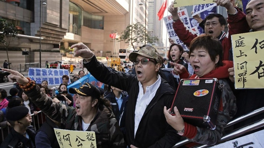 Police supporters shout slogans and hold placards to support seven Hong Kong police officers who were charged with assaulting a pro-democracy activist, outside the District Court in Hong Kong Tuesday, Feb. 14, 2017. Seven Hong Kong police officers have been found guilty of a lesser charge in the assault of a pro-democracy activist whose videotaped beating during the height of 2014 pro-democracy protests sparked outrage. A district court judge found the seven officers guilty of one joint count of assault occasioning actual bodily harm on Tuesday. (AP Photo/Kin Cheung)