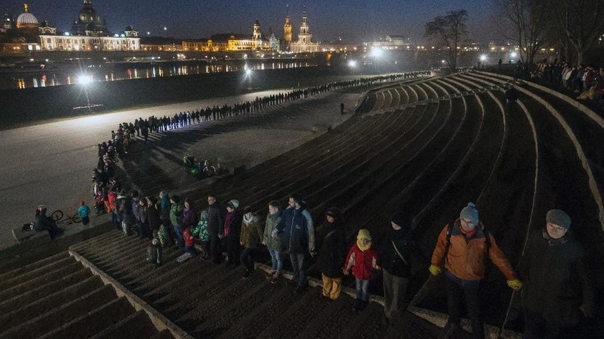 People stand along side each other to form a human chain commemorating the 72th anniversary of the deadly Allied bombing of Dresden during WWII in Dresden, eastern Germany, Monday, Feb. 13, 2017.  British and U.S. bombers on Feb. 13-14, 1945 destroyed Dresden's centuries-old baroque city center. (AP Photo/Jens Meyer)