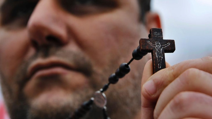 Iraqi Christian Samer Younan who lives in Lebanon holds a cross during a sit-in, in front of the United Nations Headquarters demanding speeding up their immigration cases in Beirut, Lebanon, Monday, Feb. 13, 2017. Thousands of Christians from Iraq and Syria have fled violence in their country and sought refuge in Lebanon, a religiously-mixed country. (AP Photo/Bilal Hussein)