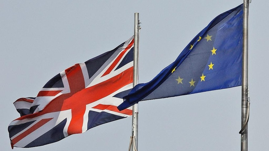 FILE - In this Thursday, Aug. 18, 2016 file photo, a Union Jack flag and a European flag blow in the wind in front of the city hall in London. A key British  business lobby is warning Britain's government not to play favorites among industries when it negotiates the country's exit from the European Union. (AP Photo/Frank Augstein, file)