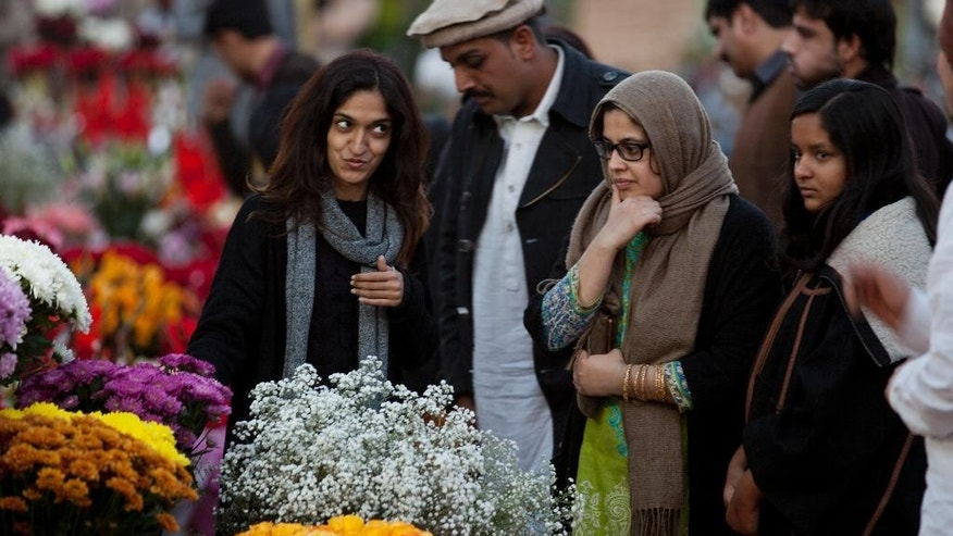 People buy flowers to celebrate Valentine's Day, in Islamabad, Pakistan, Monday, Feb. 13, 2017. A Pakistani judge has banned Valentine's Day celebrations in the country's capital, saying they are against Islamic teachings. A court official says the judge ruled on a petition seeking to ban public celebrations. Islamist and rightwing parties in Pakistan view Valentine's Day as vulgar Western import. (AP Photo/B.K. Bangash)