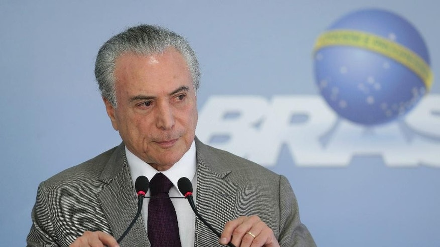 "Brazil's President Michel Temer adjusts his microphones during a press conference at the Planalto Presidential Palace, in Brasilia, Brazil, Monday, Feb. 13, 2017, where he spoke on the security vacuum created by a ""police halt"" in the Brazilian state Espirito Santo. Temer called the police halt ""an insurgency against the Constitution."" Authorities have threatened to prosecute officers who do not respond to the calls to return to duty. The Brazilian Constitution prohibits police from going on strike. (AP Photo/Eraldo Peres)"