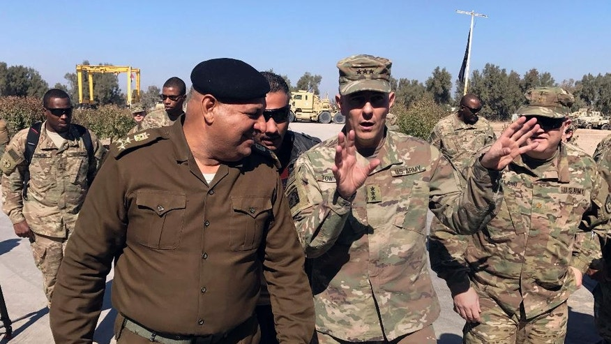 FILE - In this Wednesday, Feb. 8, 2017 file photo, U.S. Army Lt. Gen. Stephen Townsend talks with an Iraqi officer during a tour north of Baghdad, Iraq. Reverberations from President Donald Trump's travel ban and other stances are threatening to undermine future U.S.-Iraqi security cooperation, rattling a key alliance that over the past two years has slowly beaten back the Islamic State group. Iraq's prime minister, Haider al-Abadi, has sought to contain public anger sparked by the ban and by Trump's repeated statements that the Americans should have taken Iraq's oil, as well as his hard line against Iran, a close ally of Baghdad. (AP Photo/Ali Abdul Hassan, File)