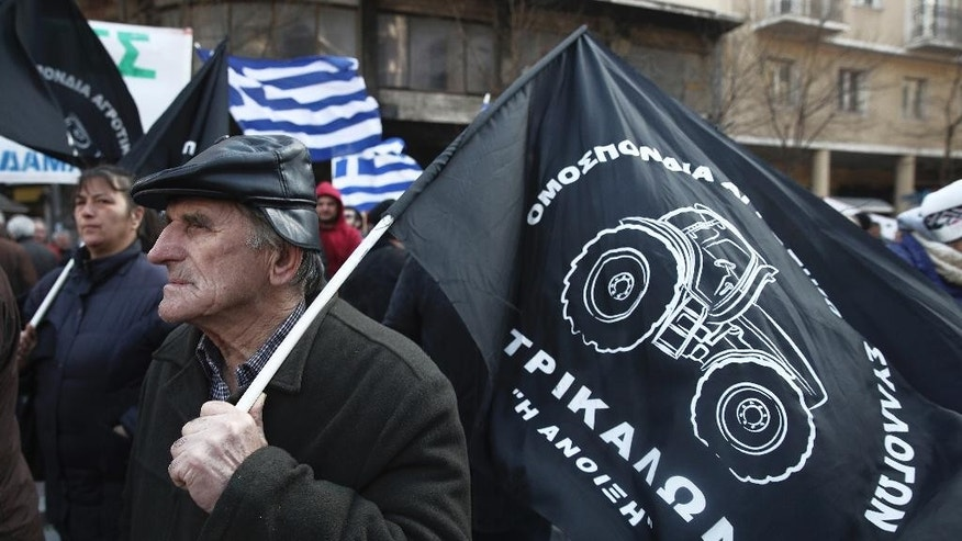 A farmer holds a flag for Trikala farmer's union during a protest in Athens, Tuesday, Feb. 14, 2017. Farming unions are angry at increases in their taxation and pension contributions, as part of Greece's bailout obligations. (AP Photo/Yorgos Karahalis)