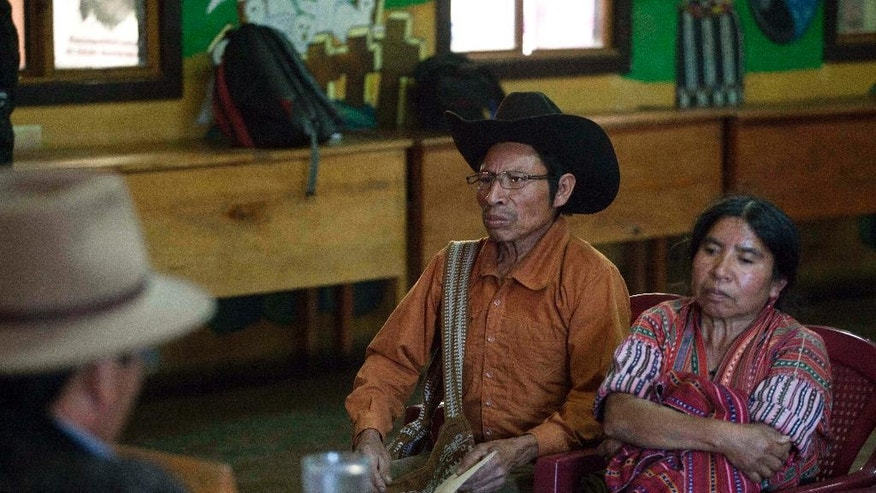 In this Jan. 16, 2017 photo, a couple listens to the arguments of indigenous judges during a hearing to resolve a land dispute at the Indigenous City Hall in Solola, Guatemala. The generally non-partisan leaders of local Mayan communities hear the cases, trying to find quick resolutions when they can and sometimes passing cases over to formal prosecutors when they cannot. (AP Photo/Moises Castillo)