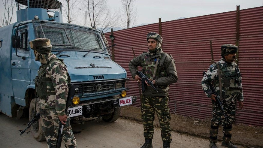 Indian paramilitary soldiers stands guard outside a base camp near the site of a gun battle with suspected rebels in Hajin Village some 38 kilometers (23.75 miles) northeast of Srinagar, Indian controlled Kashmir, Tuesday, Feb. 14, 2017. Three Indian army soldiers and a suspected rebel were killed in the gun battle in the Indian portion of Kashmir on Tuesday, officials said. (AP Photo/Dar Yasin)