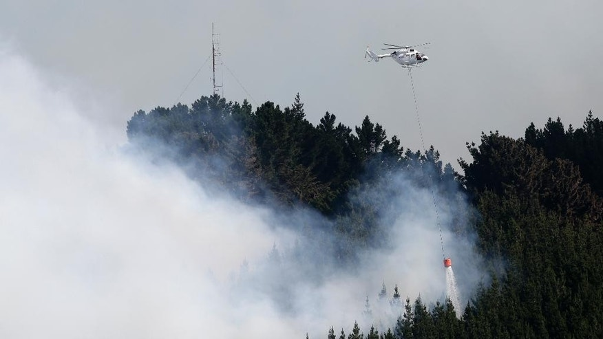 A helicopter dumps water on a wild fire in the Port Hills near Christchurch, New Zealand, Tuesday, Feb. 14, 2017. Up to 15 helicopters, and over a 100 firefighters have been battling two massive wildfires that have burnt over 700 hectares since erupting on Monday evening. (AP Photo/Mark Baker)
