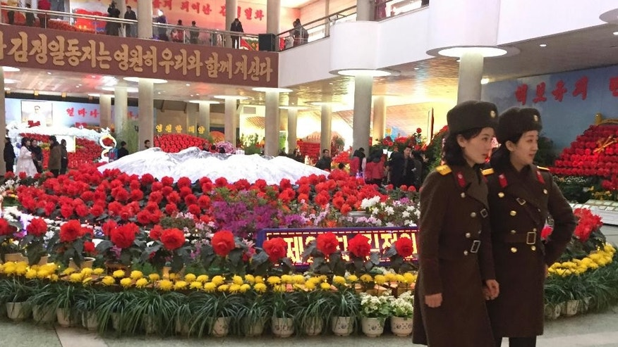 Two military guides stand near displays of flowers named after the late North Korean leader Kim Jong Il at a flower show to mark his birthday in Pyongyang, North Korea, Tuesday, Feb. 14, 2017. The annual event kicks off several days of celebrations in the North and this year also featured a depiction of the country's latest missile, which it test-launched on Sunday despite international sanctions. (AP Photo/Eric Talmadge)