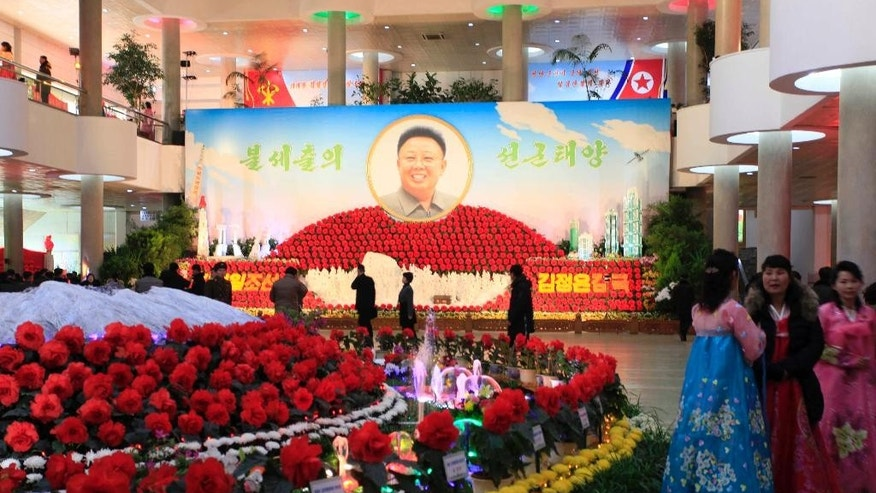 People stand near displays of flowers named after the late North Korean leader Kim Jong Il at a flower show to mark his birthday in Pyongyang, North Korea, Tuesday, Feb. 14, 2017. The annual event kicks off several days of celebrations in the North and this year also featured a depiction of the country's latest missile, which it test-launched on Sunday despite international sanctions. Kim's portrait is seen in the background. (AP Photo/Jon Chol Jin)
