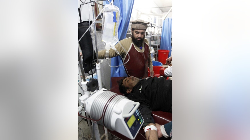 Doctor treats an injured security officer at a hospital in Peshawar, Pakistan, Wednesday, Feb. 15, 2017. A Taliban suicide bombing targeted the administrative headquarters of a tribal region in northwestern Pakistan on Wednesday, killing scores of policemen and two passers-by, according to officials. (AP Photo/Mohammad Sajjad)