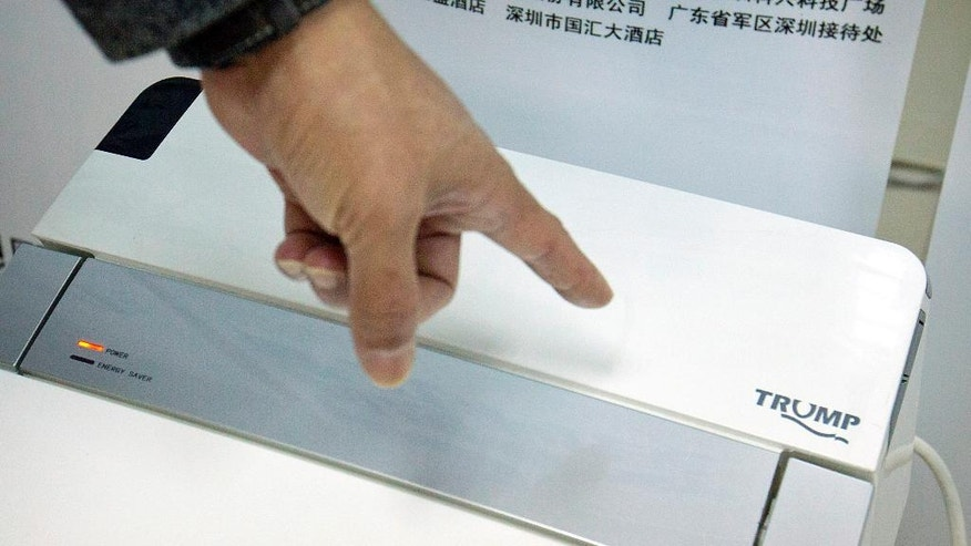 In this Monday, Feb. 13, 2017 photo, Zhong Jiye, a co-founder of Shenzhen Trump Industrial Co., points to the logo on one of his firm's high-end Trump-branded toilets at the company's offices in Shenzhen in southern China's Guangdong Province. U.S. President Donald Trump is poised to receive something that he had been trying to get from China for more than a decade: trademark rights to his own name. After suffering rejection after rejection in China's courts, he saw his prospects change dramatically after starting his presidential campaign. (AP Photo/Mark Schiefelbein)