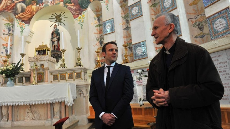 French Presidential candidate Emmanuel Macron, left, is welcomed by archbishop Paul Desfarges at the Notre-Dame d'Afrique basilica in Algiers, Tuesday Feb. 14, 2017. Macron ends his two-day visit to Algeria. (AP Photo/Anis Belghoul)
