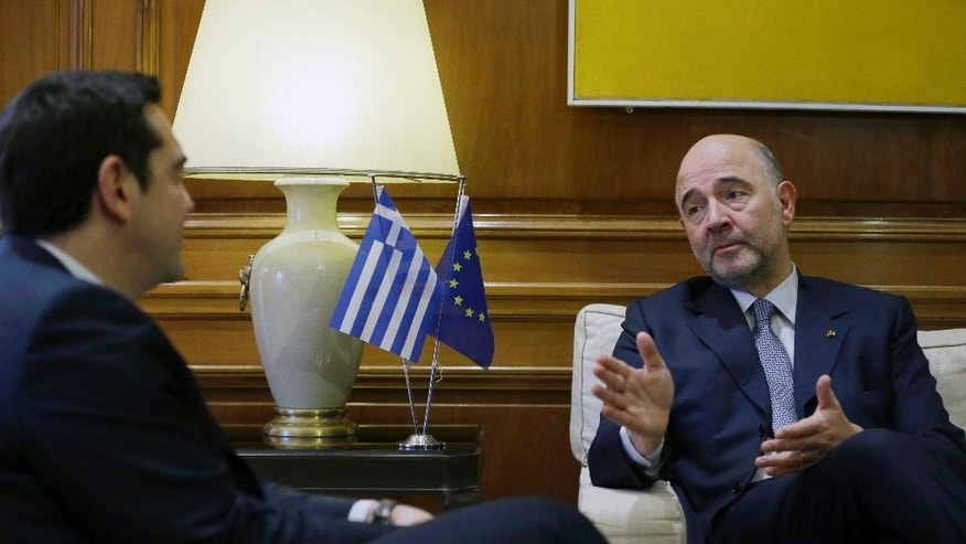 Greece's Prime Minister Alexis Tsipras, left, listens to EU Finance Commissioner Pierre Moscovici during their meeting at Maximos Mansion in Athens, Wednesday, Feb. 15, 2017. The European Union's financial affairs chief is in Greece for talks on the bailout-dependent country's slow-moving negotiations with its international creditors. (AP Photo/Thanassis Stavrakis)