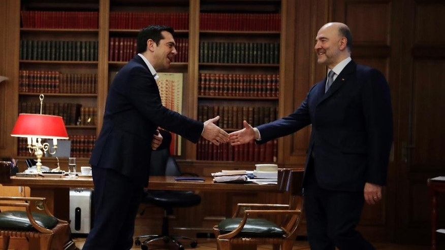 Greece's Prime Minister Alexis Tsipras, left, welcomes EU Finance Commissioner Pierre Moscovici at Maximos Mansion in Athens, Wednesday, Feb. 15, 2017. The European Union's financial affairs chief is in Greece for talks on the bailout-dependent country's slow-moving negotiations with its international creditors. (AP Photo/Thanassis Stavrakis)