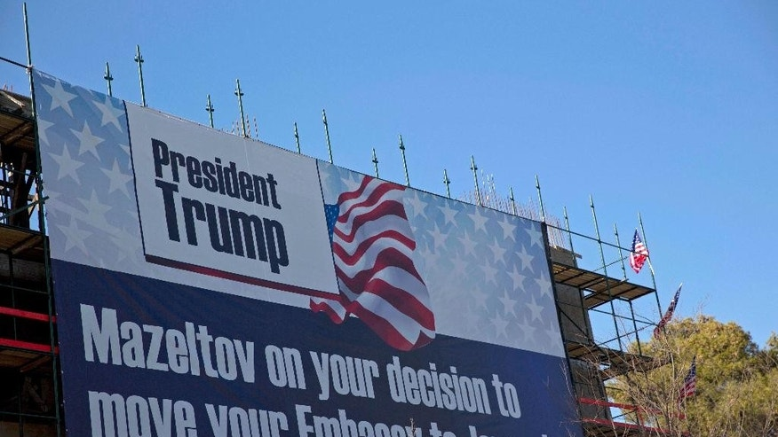 FILE -- In this Jan. 20, 2017 file photo, a sign hangs on a building under construction in Jerusalem congratulating U.S. President Donald Trump, who has vowed to move the U.S. embassy from Tel Aviv to more controversial Jerusalem. The Trump administration appears to be easing away from longstanding U.S. support for Palestinian statehood as the preferred outcome of Middle East peace efforts, which may please some allies of Prime Minister Benjamin Netanyahu in Israel. But the alternatives are few, and each comes with daunting and combustible complications, including for Israel itself. (AP Photo/Ariel Schalit, File)