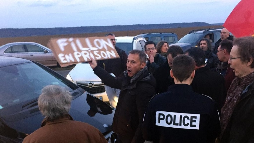 "A demonstrator holds a poster reading ""Fillon in jail"" before French conservative presidential candidate Francois Fillon' campaign meeting in Compiegne, north of Paris, Wednesday, Feb. 15, 2017. Fillon's campaign has been flailing since weekly newspaper Le Canard Enchaine revealed that his wife and children were paid public funds for allegedly fake jobs as his parliamentary aides. (AP Photo/Nadine Achoui-Lesage)"