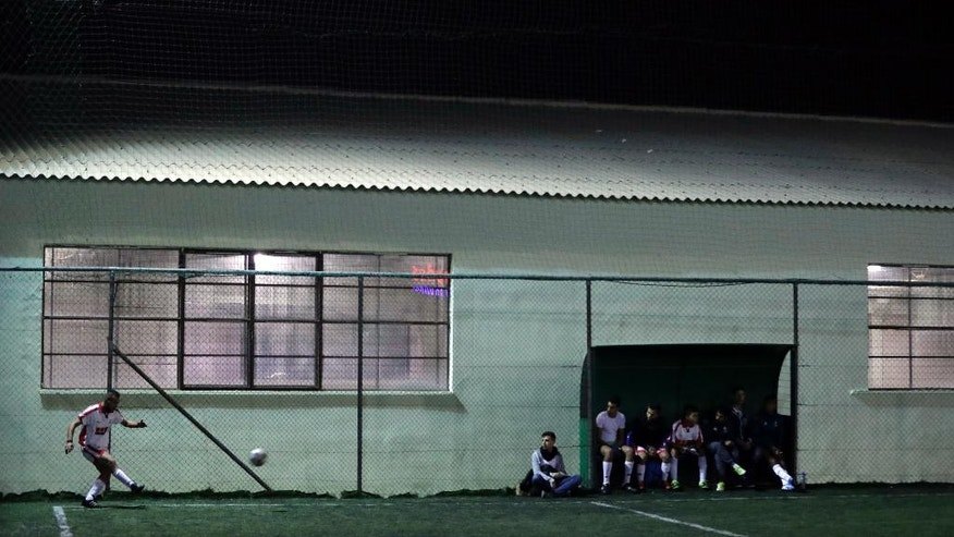 FOR STORY: GREECE TEAM CALLED HOPE - In this Sunday, Feb. 5, 2017, Syrian Hozaifa Hajdepo of Hope Refugee Football Club kicks a corner during a soccer match in western Athens. Former Greek national soccer team goalkeeper Antonis Nikopolidis, who became a national hero in 2004 during the European Cup, is heading a project to help refugees stranded in Greece regain a sense of purpose, working as a team. On weekends they play in an amateur league against teams made up of professional groups like lawyers, telecom workers, and accountants.(AP Photo/Thanassis Stavrakis)