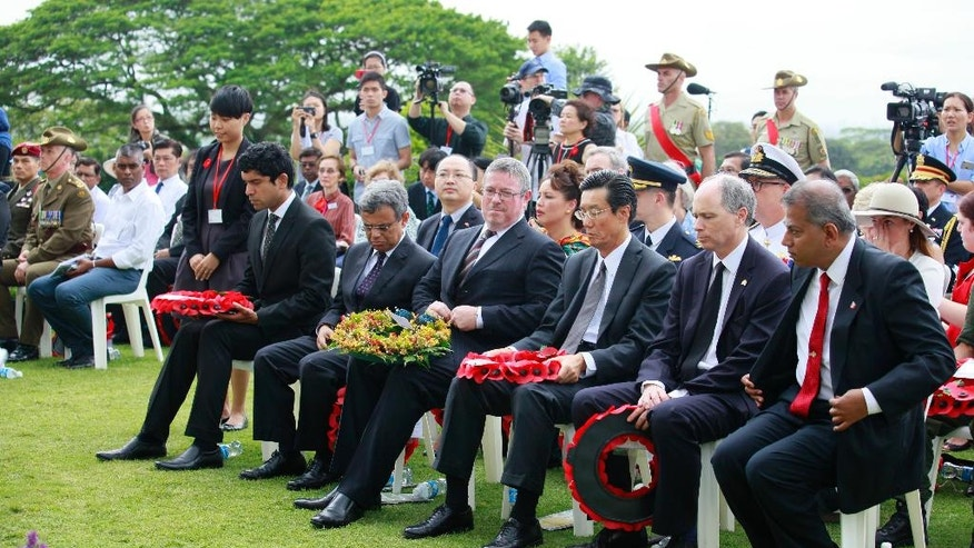 British High Commissioner Scott Wightman, second from right, Japanese Ambassador Kenji Shinoda, third from right, Australian High Commissioner Bruce Charles Gosper, fourth from right, and Indian High Commissioner Jawed Ashraf, right, hold their wreaths during a ceremony to commemorate the 75th anniversary of the fall of Singapore at the Kranji War Cemetery on Wednesday, Feb. 15, 2017, in Singapore. (AP Photo/David Loh)