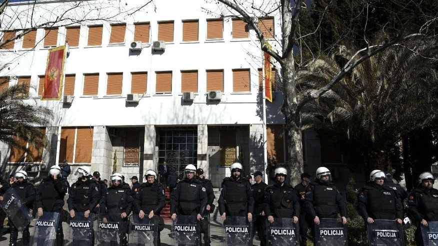 Montenegro riot police guard the Parliament building during an anti-government protest in Podgorica, Montenegro, Wednesday, Feb. 15, 2017. Montenegrin lawmakers voted on Wednesday to lift the immunity of two key opposition leaders allegedly involved in a pro-Russian plot to overthrow the government over its NATO bid. (AP Photo/Risto Bozovic)