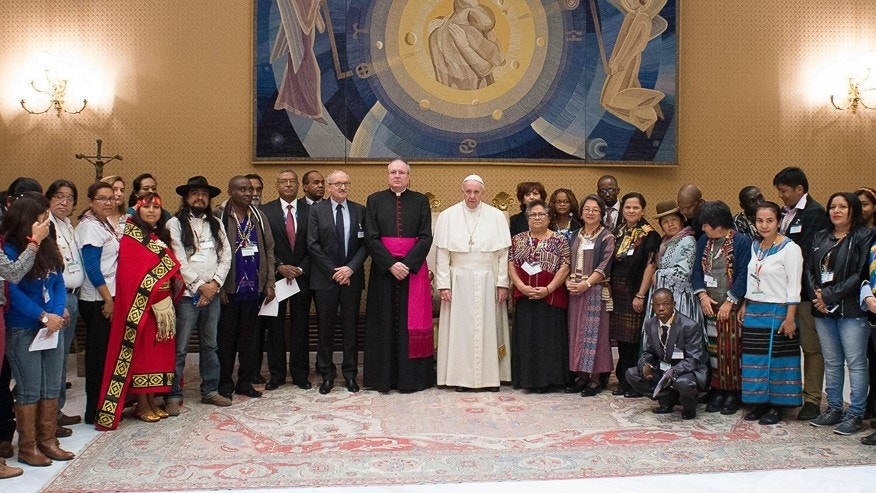 Pope Francis, center, poses with representatives of indigenous peoples attending a UN agricultural meeting in Rome, at the Vatican, Wednesday, Feb. 15, 2017. Francis has insisted that indigenous peoples must give prior consent for any economic activity on their ancestral lands — an indirect critique as the Donald Trump administration seeks to advance construction on a $3.8 billion oil pipeline over opposition from American Indians. (L'Osservatore Romano/Pool Photo via AP)