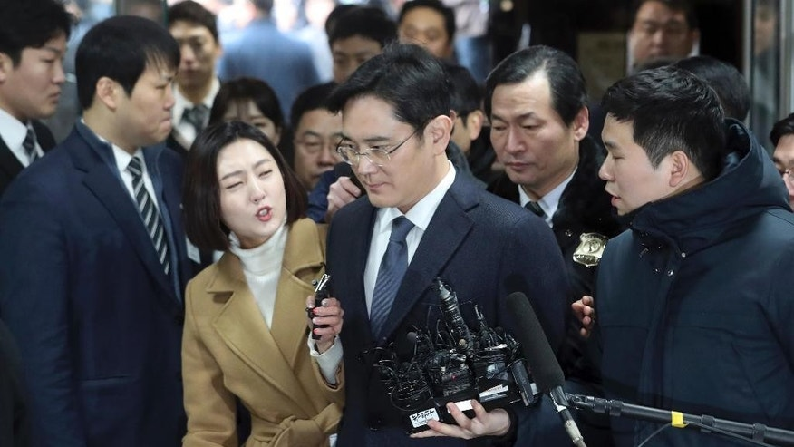 Lee Jae-yong, the vice chairman of Samsung Electronics, center, is questioned by reporters upon his arrival for a hearing at the Seoul Central District Court in Seoul, South Korea, Thursday, Feb. 16, 2017. A South Korean court has begun deliberating on whether to issue an arrest warrant for the Samsung heir accused of offering bribes to the country's president and her close friend. Lee walked into the court on Thursday without speaking. (Choi Jae-gu/Yonhap via AP)