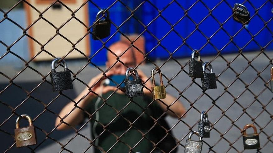 "In this Friday, June 24, 2016 file photo, a journalist takes pictures of padlocks left on a fence of Metris prison, during a demonstration of people demanding the release of Reporters Without Borders' local representative Erol Onderoglu, academic Sebnem Korur Fincanci and journalist Ahmet Nesin, outside Metris prison where Onderoglu and Nesin were held, in Istanbul. Council of Europe, the continent's top human rights institution urged Turkey's leaders Wednesday, Feb. 15, 2017 to ""urgently change course"" and reverse violations of media freedoms and the rule of law, voicing alarm over democracy in the country. (AP Photo/Lefteris Pitarakis, File)"