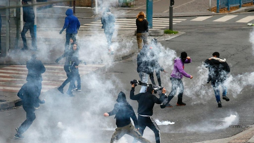 Youth run away from tear gas during a protest against alleged police abuse, Thursday, Feb. 16, 2017 in Bobigny, north of Paris. French authorities have launched Tuesday a new investigation into alleged police abuse by an officer already accused in a rape case that sparked a week of scattered violence in the troubled suburbs of Paris. (AP Photo/Francois Mori)
