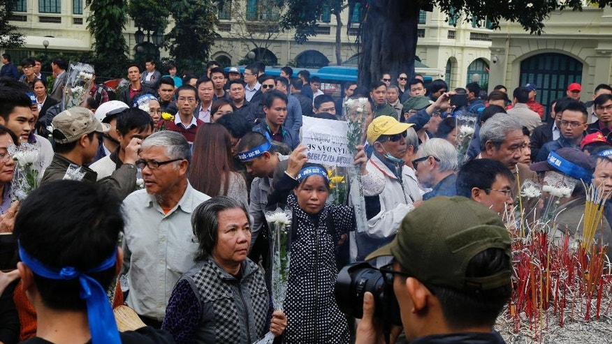 Dozens gather in front of the statue of the 11th century founding father of Hanoi King Ly Thai To in central Hanoi, Vietnam, Friday, Feb. 17, 2017. Several dozen people gathered to commemorate the brief but bloody border war with China 38 years ago. (AP Photo/Tran Van Minh)