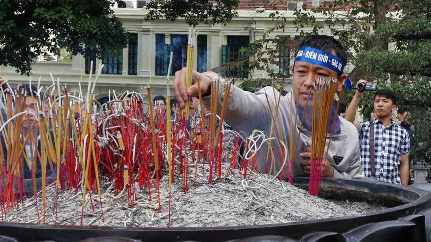 A man places incense while others pray in front of the statue of the 11th century founding father of Hanoi King Ly Thai To in central Hanoi, Vietnam, Friday, Feb. 17, 2017. Several dozen people gathered to commemorate the brief but bloody border war with China 38 years ago. (AP Photo/Tran Van Minh)
