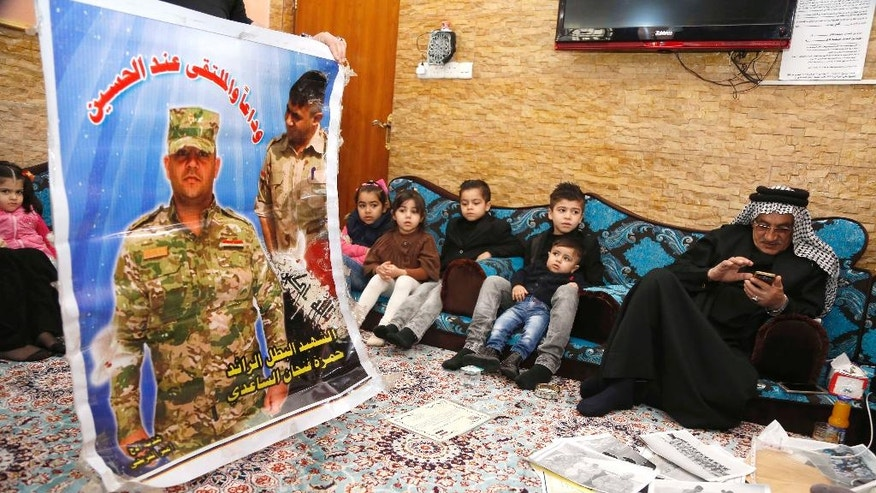 In this Monday, Feb. 6, 2017 photo, Fenjan Jerry Mady, right, the father of Hamza Finjan, an Iraqi officer killed in Mosul fighting Islamic State militants, seen in the poster, sits with his family in Baghdad, Iraq. As Iraqi forces prepare for the operation to retake western Mosul, Hamza Finjan's family mourns their son in Baghdad more than 300 kilometers (185 miles) away. Hundreds of Iraqi soldiers are estimated to have died in the fight for Mosul so far, but the Iraqi government does not release official casualty reports, a move that many Iraqis view as disrespectful of their sacrifice.(AP Photo/ Karim Kadim)