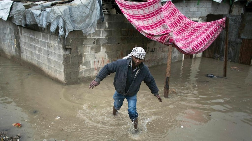 A Palestinian man walks out of his flooded makeshift house during a heavy rain storm in Jabaliya refugee camp, northern Gaza Strip, Thursday, Feb. 16, 2017 (AP Photo/ Khalil Hamra)