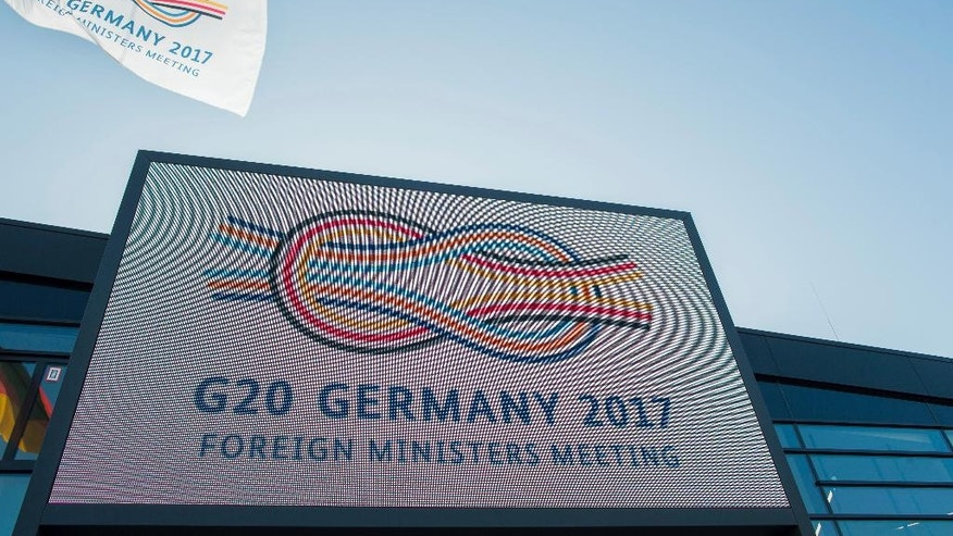 The logo 'G20 Germany 2017' is lit up outside the World Conference Center in Bonn, Germany, Wednesday, Feb 15 2017. The foreign minister of the G20 countries are meeting Feb. 16 and 17, 2017 in Bonn. (Rolf Vennenbernd/dpa via AP)