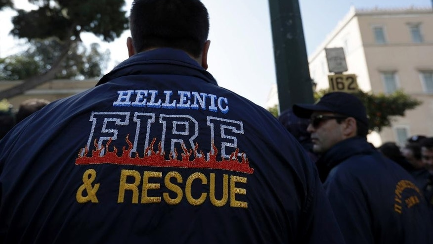 Firefighters take part in a protest outside parliament amid a contract dispute with the cash-strapped government, in Athens on Thursday, Feb. 16, 2017. The government says it is lacking the funds needed to offer thousands of firefighters long-term contracts. Greece is under pressure to make deeper spending cuts as it struggles to reach agreement with bailout lenders on the terms of future loan payouts. (AP Photo/Thanassis Stavrakis)